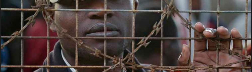 Black prisoner behind barbed wire